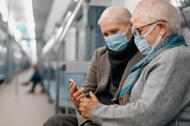 地下鉄の車に座っているスマートフォンの画面を見ている2人の成熟した女性