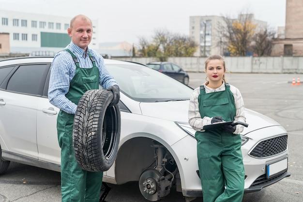 Two mechanics examining brake disk in car