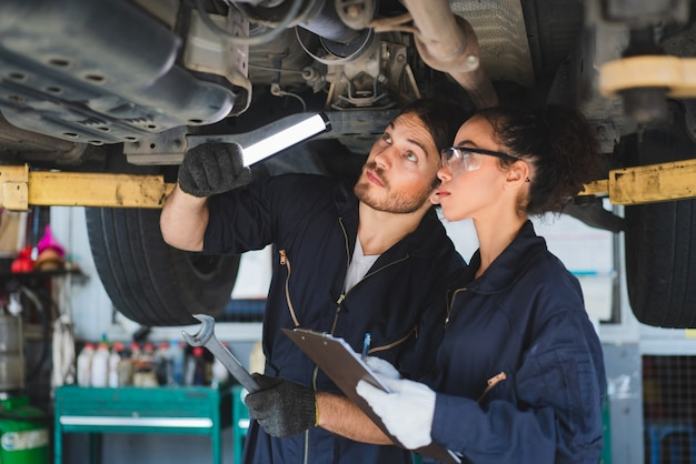 Two mechanics man and woman checking and repair maintenance a car in auto service garage