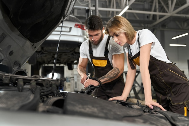 Two mechanics repairing car in professional autoservice.