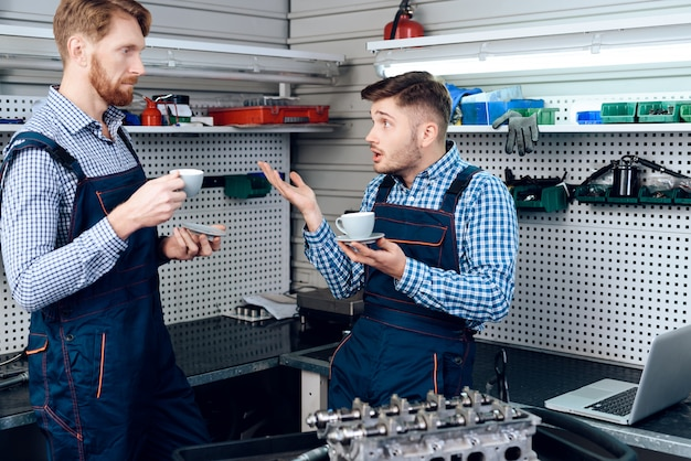 Two mechanics on service station. coffee drinking.