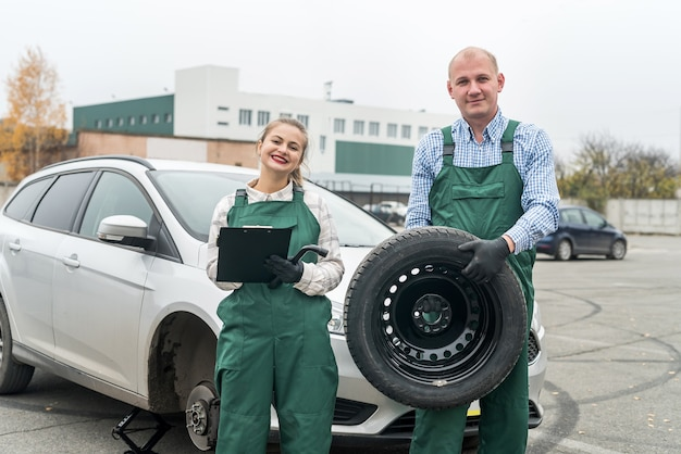 Two mechanics with tyre and clipboard near car