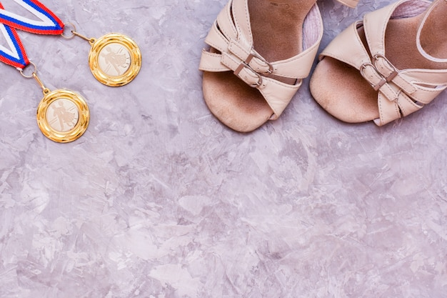 Two medals on the ribbon and shoes for sports ballroom dancing, top view