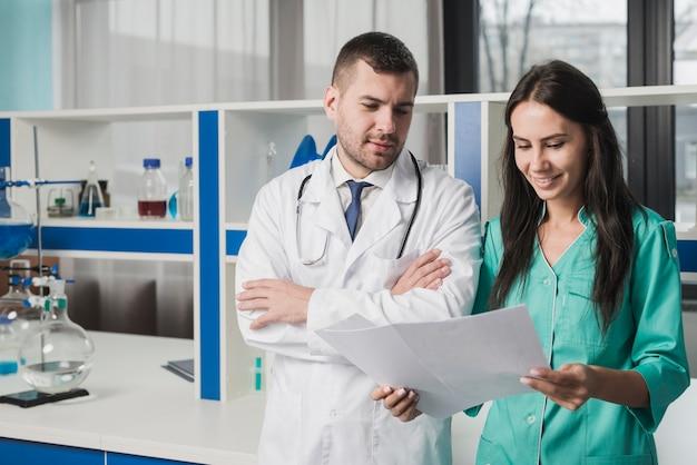 Two medics reading paper