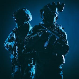 육군 엘리트 부대의 두 구성원, 현대 전술 탄약을 갖춘 전투복을 입은 대테러 부대 병사, 무장 서비스 소총, 어깨를 나란히 하고 함께 서 있는, 낮은 키 스튜디오 촬영