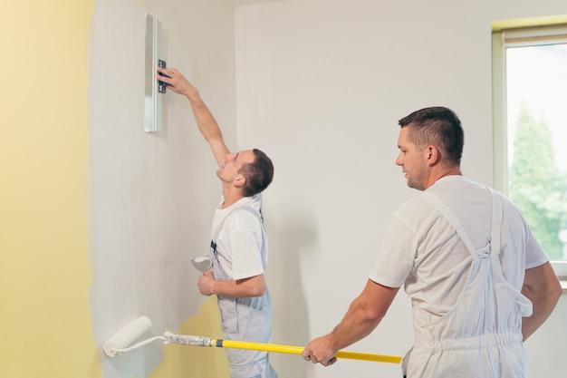 Двое мужчин наносят штукатурку на стену и ремонтируют дом