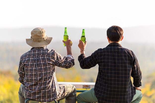 Двое мужчин - друзья, ведущие здоровый образ жизни и отдыхающие, подбадривая с пивом и выпивая пиво
