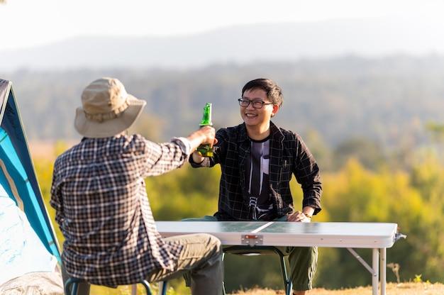 二人の男は健康的なライフスタイルを生きている友人であり、ビールとビールを飲みながら応援をリラックス