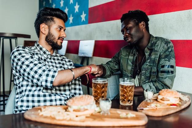 2人の男性がバーまたはレストランのラウンジで一緒に座っていますお互いに手を差し伸べます