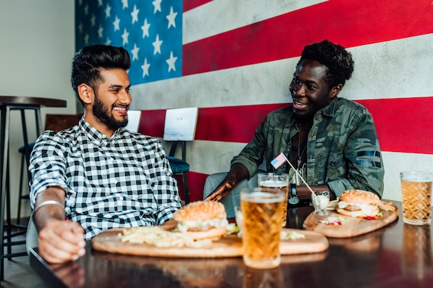 2人の男性がバーまたはレストランのラウンジに一緒に座っています。彼らはハンバーガーとビールを楽しみながら笑ったり話したりしています