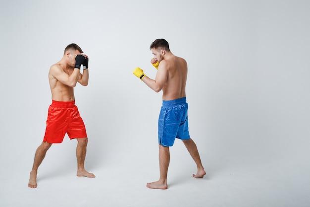 Двое мужчин боксеров борются с тайским боксом на белом фоне.
