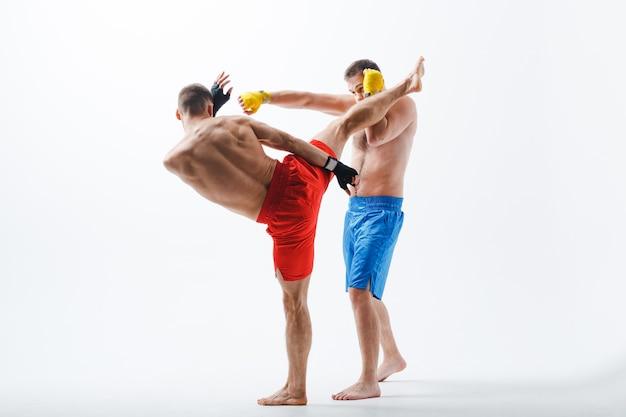 Двое боксеров борются по муай тай кикбоксингу hgh kick на белом фоне