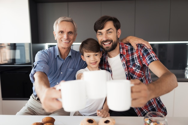 Two men and a boy are posing in the kitchen with cups