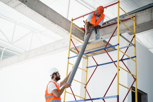 Two men builder in uniform drag the pipe on scaffolding at construction site