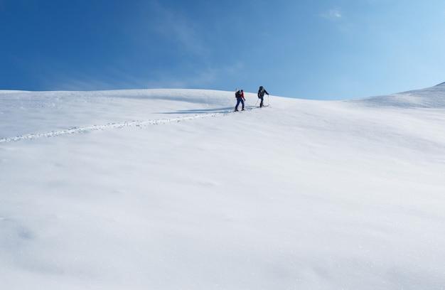 스키 나 스플릿 보드를 타고 산 정상에 오르는 두 남자. 스키 투어링