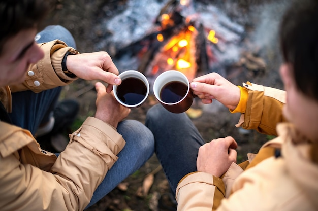 Two men clincking with cups of coffee on a picnic, campfire in front of them