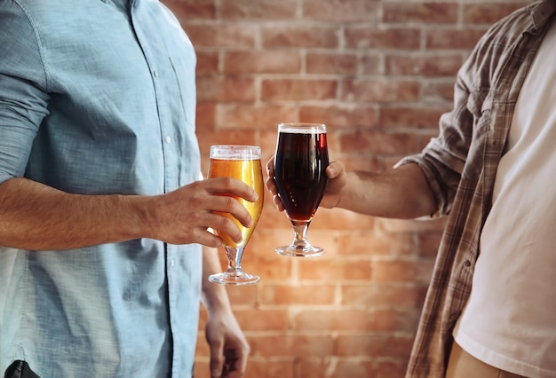Two men clinking glasses of dark and light beer on brick wall