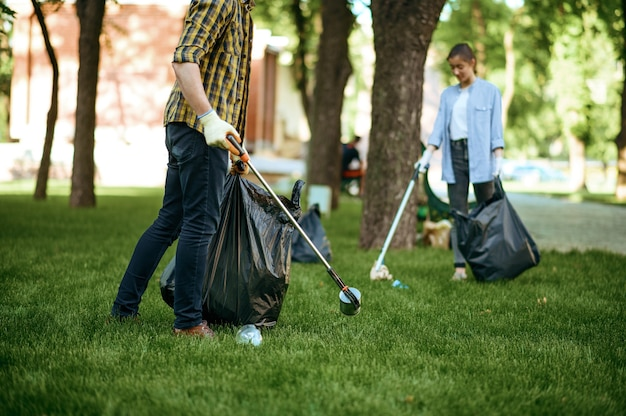 Two men collects plastic garbage in bags in park, volunteering. male person cleans forest, ecological restoration, eco lifestyle, trash collection and recycling, ecology care, environment cleaning
