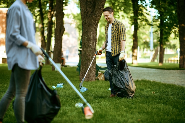 Two men collects plastic garbage in bags in park, volunteering