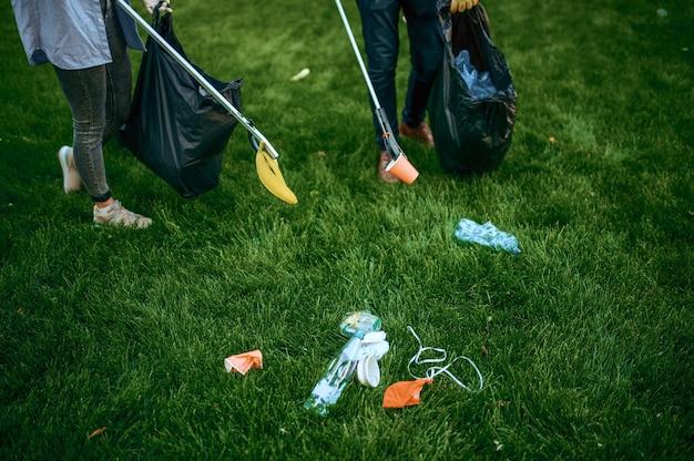 Двое мужчин собирают пластиковый мусор в пакеты в парке, занимаются волонтерством