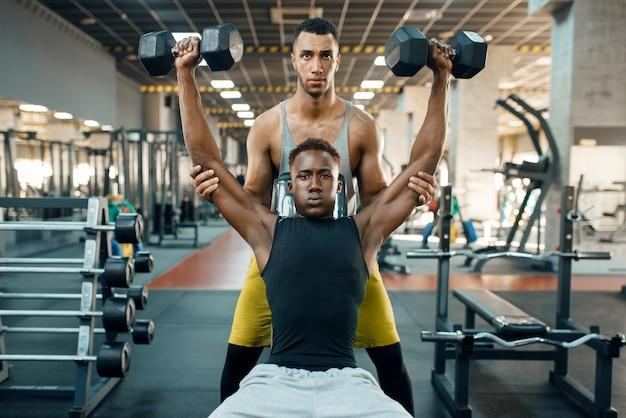 Двое мужчин делают упражнения с гантелями на скамейке, тренируются в тренажерном зале