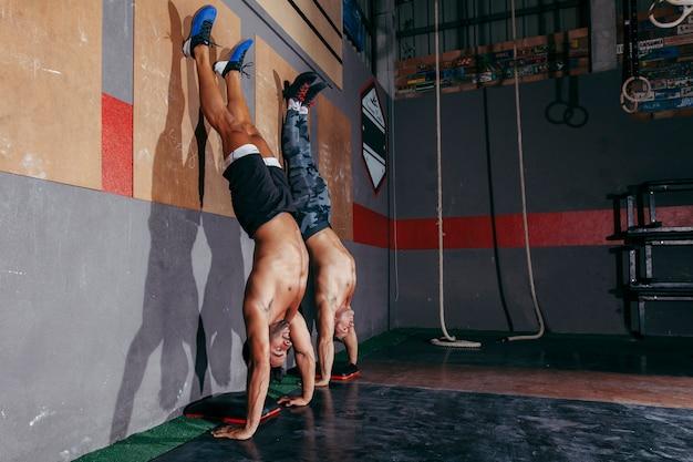 Two men doing handstands in gym