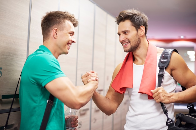 Two men in dressing room at gym