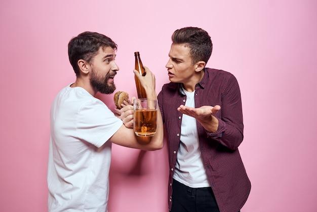 Двое мужчин пьют пиво дружба пьяный алкоголь образ жизни розовый фон. фото высокого качества