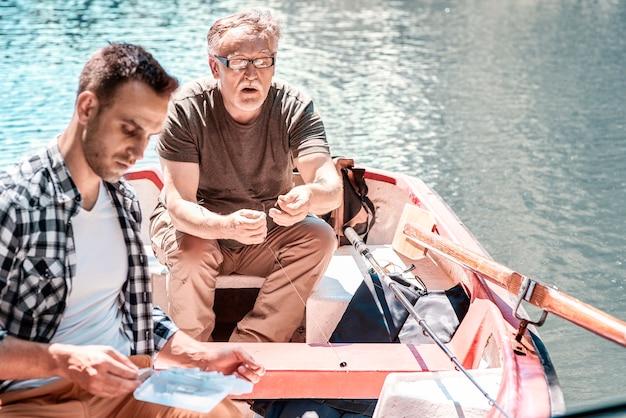 Двое мужчин занимаются рыбалкой