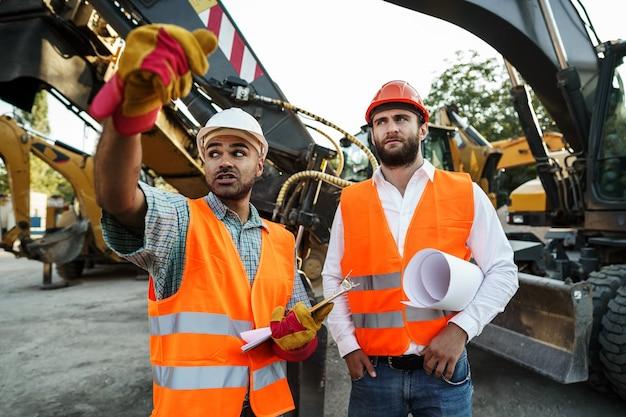 Двое мужчин-инженеров обсуждают свою работу, стоя против строительных машин