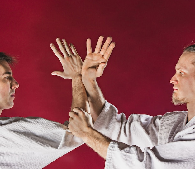 Two men fighting at aikido training in martial arts school. healthy lifestyle and sports concept. men in white kimono on red background. male hands closeup on red studio background