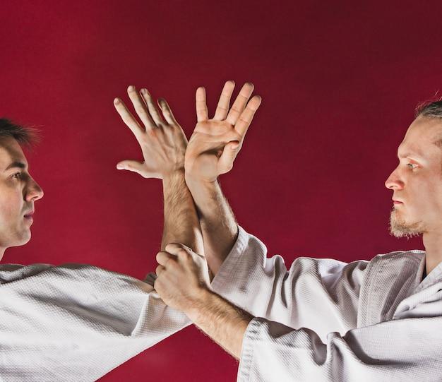 武道学校の合気道訓練で戦う二人の男。健康的なライフスタイルとスポーツのコンセプト。赤い背景に白い着物の男性。赤いスタジオの背景に男性の手のクローズアップ