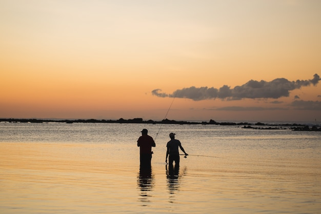 Two men fishing in the ocean from the beach at sunset