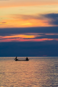 Two men fishing on the sea under sunset.