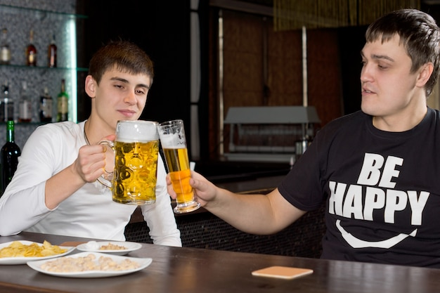 Two men friends drinking beer together in a pub sitting at the counter raising their tankards in a toast