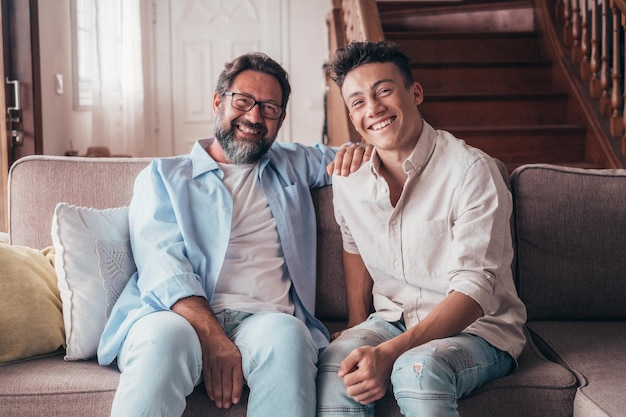 두 남자는 소파에서 가정 생활을 즐기고 카메라를 보며 웃고 있습니다. 아빠와 아들 관계는 실내에서 웃고 있습니다.