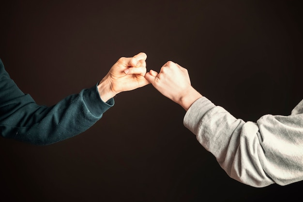 Two men hold their little fingers and make peace d s