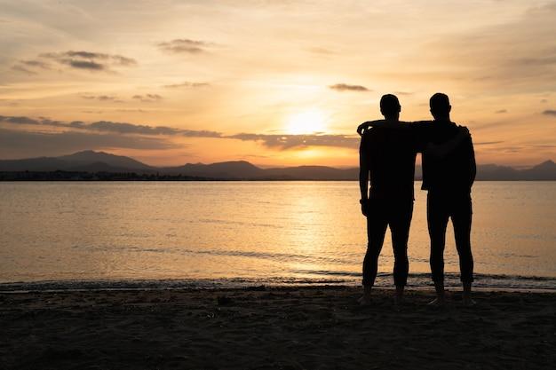 Двое мужчин держат друг друга одной рукой, наблюдая за закатом