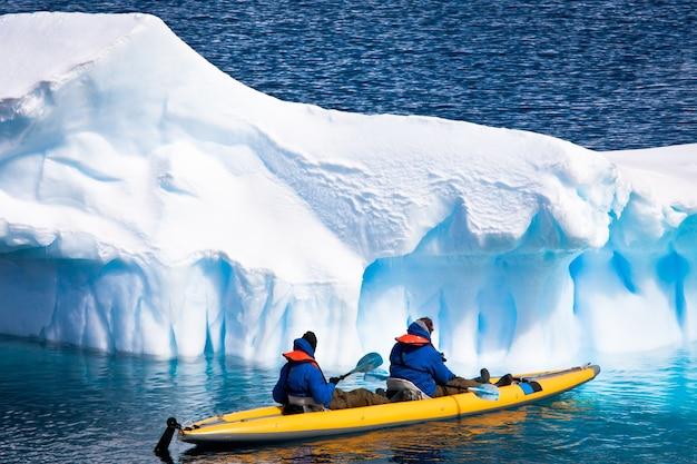 南極の氷山の間でカヌーに乗った2人の男性
