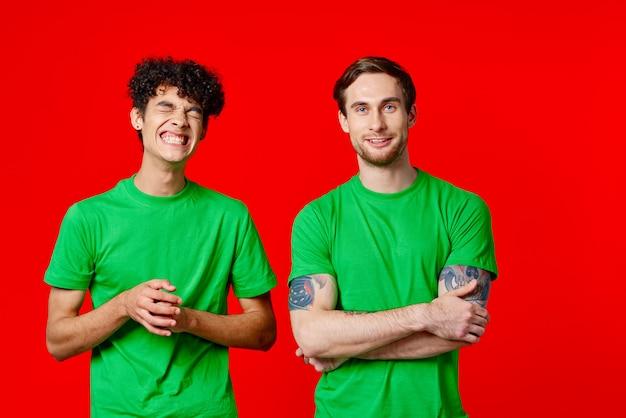 緑の t シャツを着た 2 人の男性が友情の赤い背景の隣に立っています。