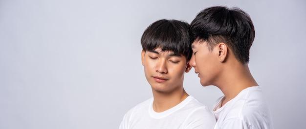 白いtシャツを着ている恋に落ちた2人の男性がお互いの顔を見ました。
