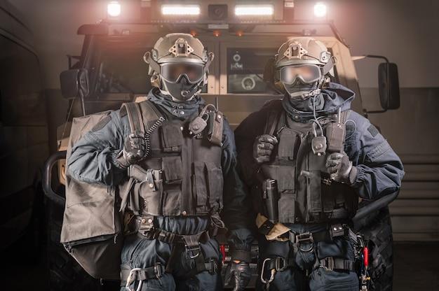 Двое мужчин в военной форме стоят в ангаре с грузовиком