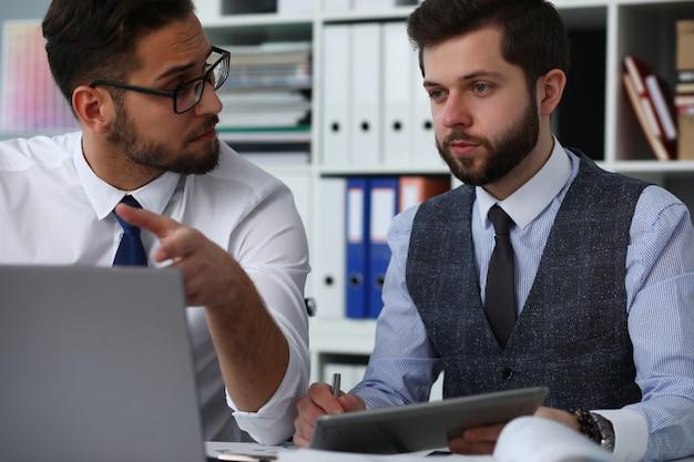 Двое мужчин в офисе с помощью ноутбука и общения