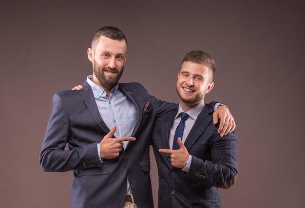 Двое мужчин в костюмах обнимаются и указывают пальцем друг на друга