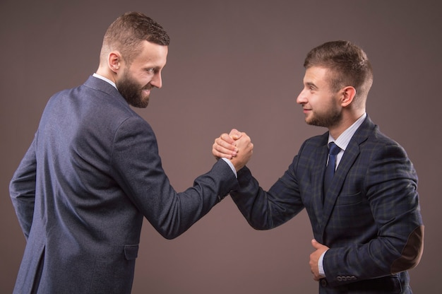 서로의 눈을 들여다보고 팔에서 고군분투하는 정장을 입은 두 남자