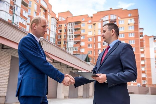 Двое мужчин в костюмах с буфером обмена и ключами ведут переговоры