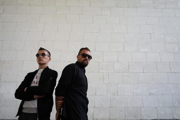 벽돌 벽 배경에 선글라스를 쓴 두 남자