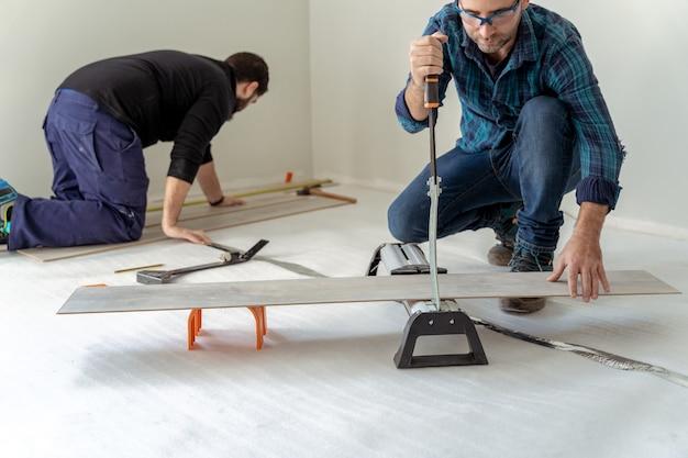 나무 바닥을 설치하는 두 남자가 하나는 보드를 자르고 다른 하나는 나무 바닥을 설치하고 있습니다
