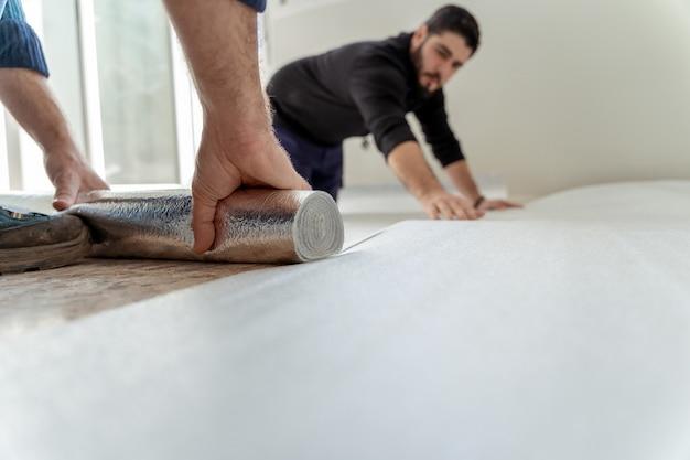 집 리노베이션에 나무 바닥 설치를 위해 바닥 라미네이트를 설치하는 두 남자