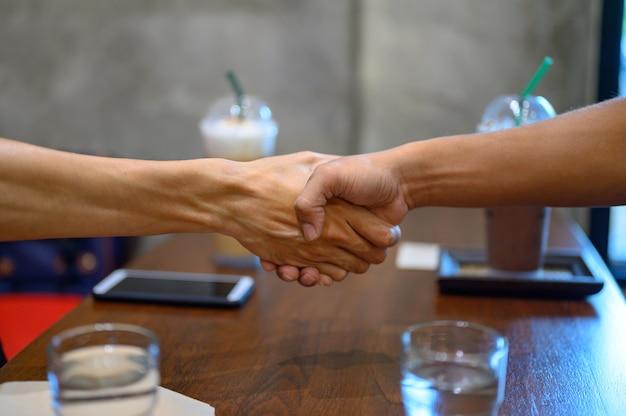 Двое мужчин взялись за руки для делового сотрудничества